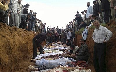 This citizen journalist image obtained by the Associated Press on Friday, April 6, 2012. purportedly shows a mass burial of people allegedly killed in recent shelling in Taftnaz, Syria. (photo credit: AP)