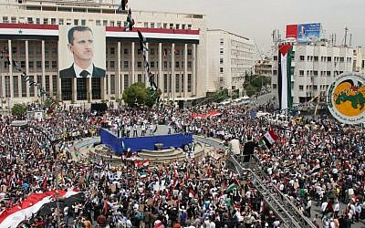 Pro-Syrian government demonstrators hold a rally in Damascus to commemorate the 65th anniversary of the foundation of the ruling Baath Arab Socialist Party, April 7, 2012. (photo credit: AP Photo Bassem Tellawi)