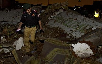 Pakistani rescue workers amid wreckage of the Boeing 737 passenger plane which crashed in the outskirts of Islamabad. (photo credit: AP)