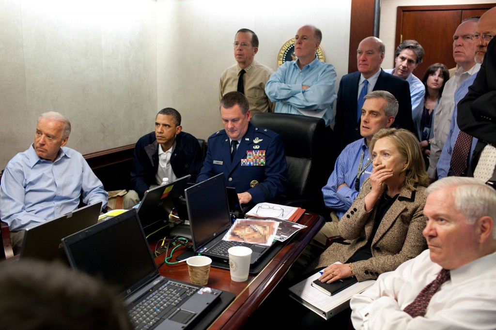 US Secretary of State Hillary Rodham Clinton, at right with hand covering mouth, President Barack Obama, second from left, Vice President Joe Biden, left, Secretary of Defense Robert Gates, right, and members of the national security team watch an update on the mission against Osama bin Laden in the White House Situation Room on May 1, 2011. The image, released by the White House, was digitally altered by the source to obscure the details of a document in front of Secretary Clinton. (photo credit: AP Photo/The White House, Pete Souza)