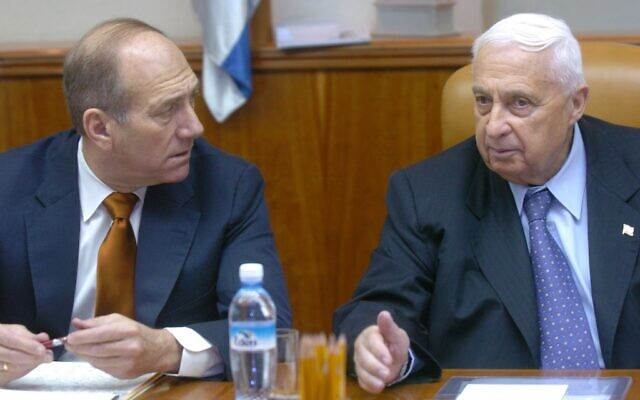 Ehud Olmert and Ariel Sharon, at a 2004 cabinet meeting. (photo credit: Sharon Perry/Flash 90/File.