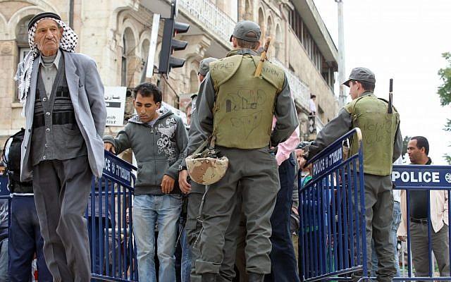 Arab men walk by border police next to Damascus gate in Jerusalem's Old City (photo credit: Nati Shohat/Flash90)