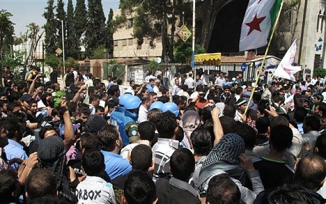 Syrian protestors gather around U.N. observers during their visit in Douma near the capital of Damascus, Syria, April 23, 2012 (photo credit: AP)
