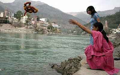 A woman throws a garland of flowers into the Ganges (photo credit: Liron Almog/Flash90)
