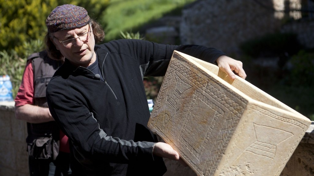 Documentary filmmaker Simcha Jacobovici shows a life-size replica of one of the ossuaries found in 'Patio Tomb', a first century burial cave located beneath an apartment building on April 4, 2012 in Jerusalem,Israel. The artifacts, believed to date from the first century, are the subject of Jacobovici's documentary The Resurrection Tomb, which aims to unearth new findings on Jesus' earliest followers. The limestone Jewish ossuaries, or 'bone boxes', were captured on film using a camera on a robotic arm and have prompted scepticism from certain quarters over the objects' veracity. PHOTO BY Lior Mizrahi / FLASH 90