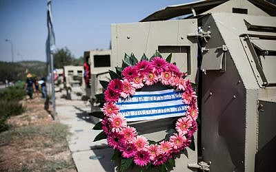 A wreath and flags on the remains of armored vehicles, which stand as a memorial monument from the War of Independence along the main road to Jerusalem. (photo credit: Noam Moskowitz/Flash90)