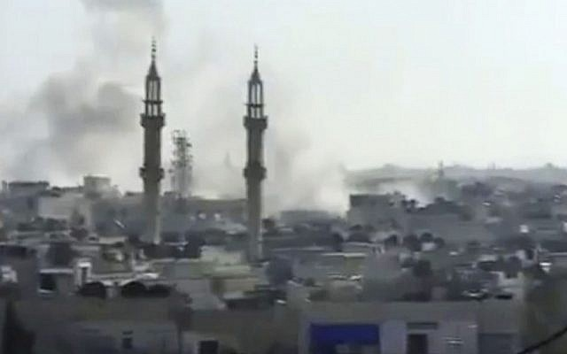 Smoke rising from buildings in Homs, Syria, in April 2012 (photo credit: AP/Shaam News Network via AP video)