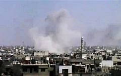 In this image made from amateur video released by the Syrian Media Council, smoke rises following purported shelling in Homs, Syria. (Photo credit: AP Photo/Syrian Media Council via AP video)