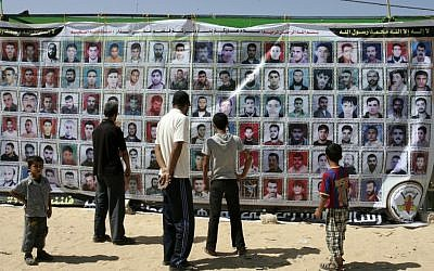 Gazans stand in front of a banner showing portraits of Palestinians held in Israeli jails in October 2011 in Rafah, in the southern Gaza Strip (photo credit: Abed Rahim Khatib/Flash 90)