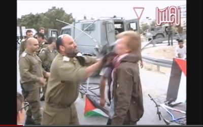 Lt.-Col. Shalom Eisner strikes a Danish protester with his rifle. (photo capture from ISM video on Youtube)