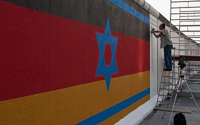 Berlin Wall mural, originally painted in 1988 by Günther Schaefer as a reminder of the 40th anniversary of the Kristallnacht pogrom in Nazi Germany. The mural features an Israeli flag superimposed on a German one. (photo credit: CC-BY-SA Maartmeester, Flickr)