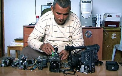 Co-director Emad Burnat with his five broken cameras. (photo credit: Kino Lorber)