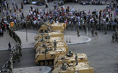 Armored Egyptian military vehicles block the road outside of the Ministry of Defense in Cairo, Friday. (photo credit: AP/Ahmed Hammad)