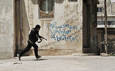 A Syrian rebel runs for cover in Homs (photo credit: AP/Fadi Zaidan/File)