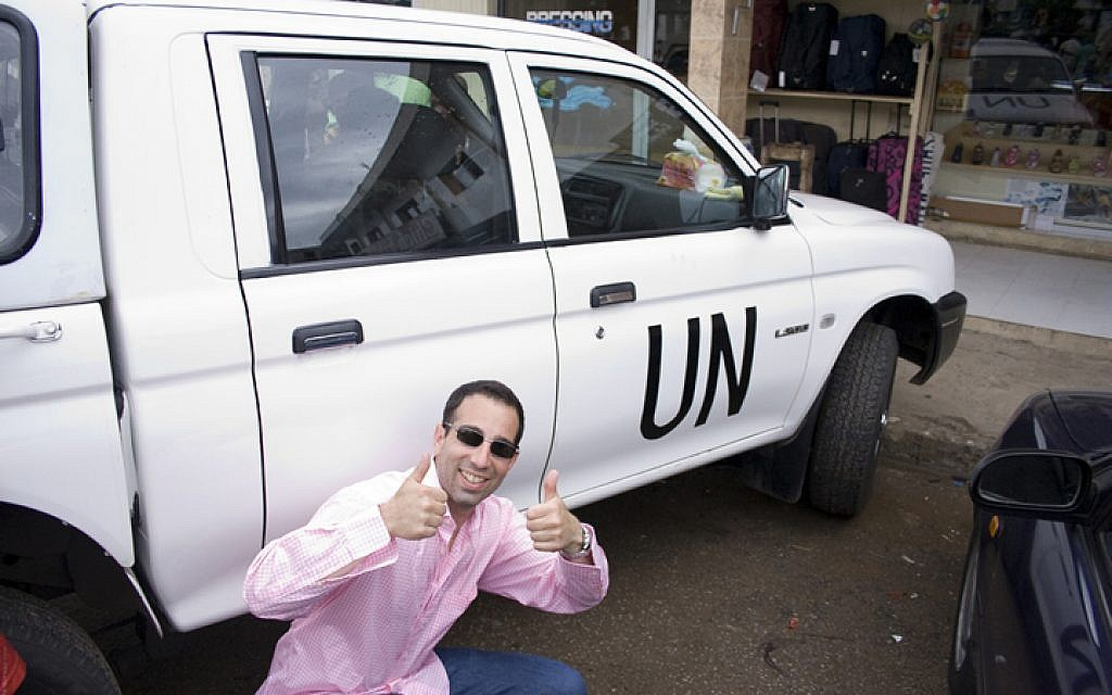 Ami Horowitz, director of the film 'U.N. Me,' next to a UN car in Cote d'Ivoire. (Photo credit: Frank Publicity/JTA)