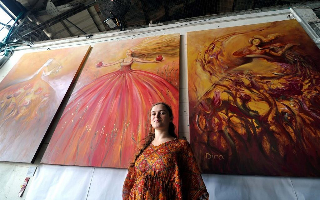 Dina Argov, at the Container restaurant/artspace in Jaffa, with her triptych 'Painting Women' behind her (photo credit: David Katz)