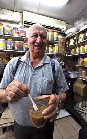 Zion Arama, of Arama cafe, with a fresh brew of white Yemeni coffee in his hand (photo credit: David Katz)