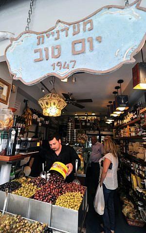 Eitan Yom Tov replenishes a quick-depleting batch of olives at the Yom Tov Delicatessen (photo credit: David Katz)