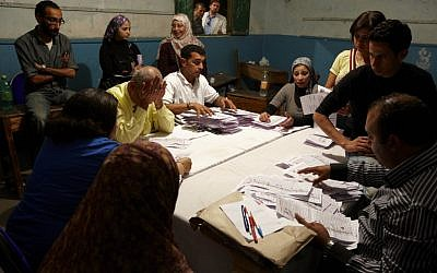 Election workers counting voted in Cairo Thursday. (photo credit: AP/Fredrik Persson)