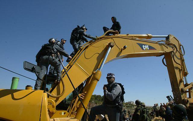 Israeli police atop a Caterpillar bulldozer during a demonstration against the security barrier. (photo credit: Ahmad Gharabli / Flash90)