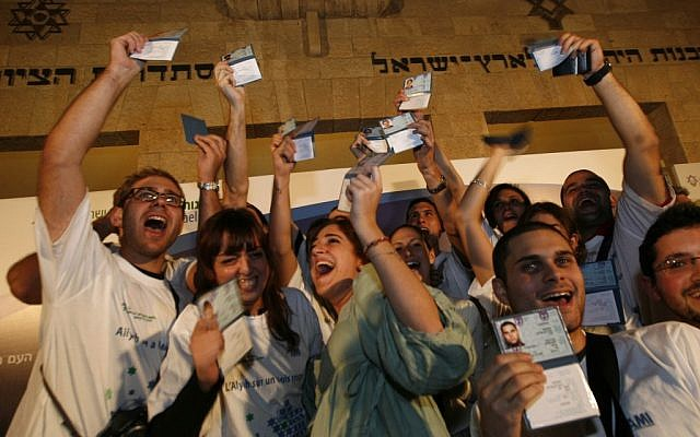 New immigrants to Israel from France hold up their new Israeli ID cards (photo credit: Miriam Alster/Flash90)