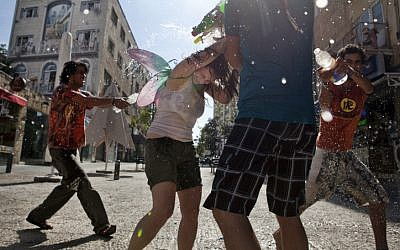 Children spray water at each other during a water fight in Jerusalem (photo credit: Matanya Tausig/Flash90)