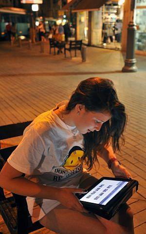 A teenager girl surfs the internet in Jerusalem. (illustrative photo credit: Serge Attal/Flash90)
