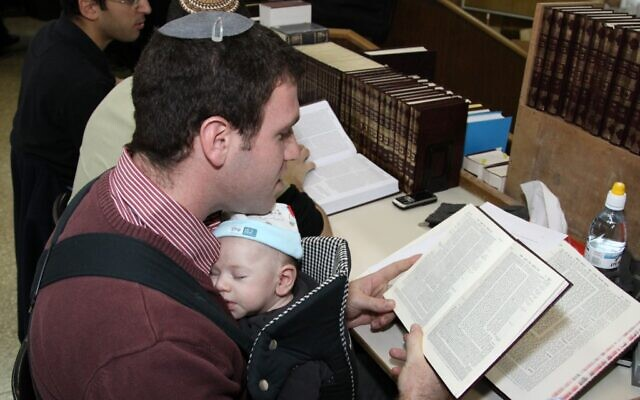 A father wearing his baby while learning (photo credit: Gershon Elinson/Flash 90)