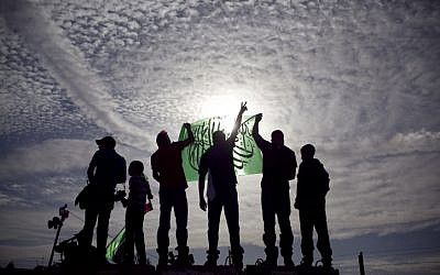Palestinians hold up Hamas flags (photo credit: Matanya Tausig/Flash90)