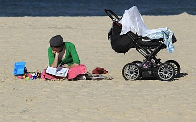 An ultra-Orthodox woman reads a book next to her baby carriage on the beach (photo credit: Tsafrir Abayov/Flash90)