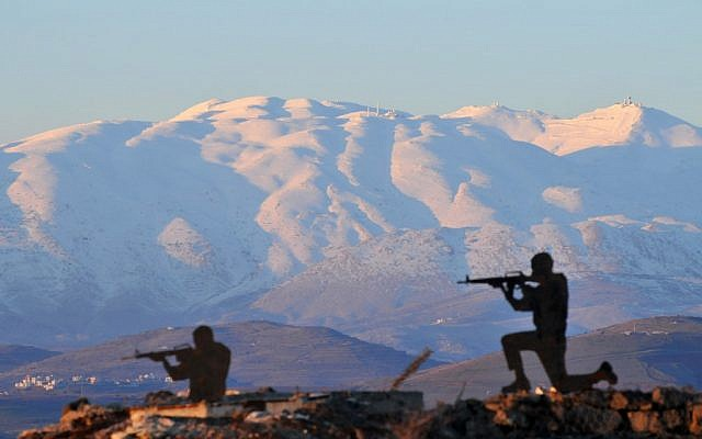 Metal silhouettes of soldiers dot the landscape overlooking the snow-covered Mount Hermon in the Golan Heights in January. (photo credit: Shay Levy/Flash 90)