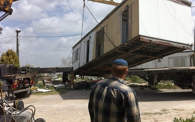 A Jewish settler watches as a mobile home is moved from the illegal outpost of Ramat Gilad in March. (photo credit: Roy Sharon/Flash90)