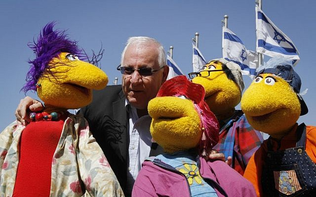 Knesset Speaker Reuven Rivlin poses with dolls from a children's TV show. (photo credit: Miriam Alster/Flash90)