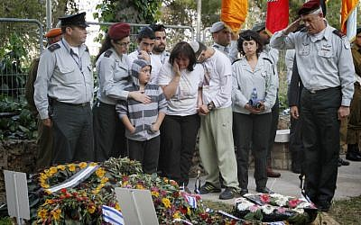 Friends and relatives of Hila Betzaleli cry as IDF Chief of General Staff Benny Gantz salutes after laying an Israeli flag on her grave, at the Mount Herzl military cemetery (photo credit: Miriam Alster/Flash90)