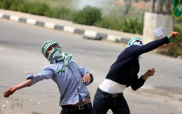 Palestinian protesters throw stones at Israeli troops outside the Ofer military prison near Ramallah on Wednesday. (photo credit: Issam Rimawi/Flash90)