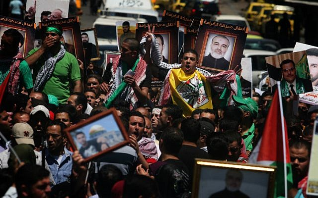 Protesters in Ramallah hold pictures of Palestinians jailed in Israel during a rally in solidarity with hunger strikers in 2012. (photo credit:  Issam Rimawi/Flash90)