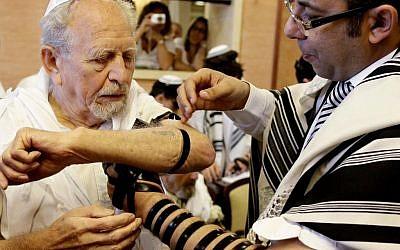 A Holocaust survivor wraps tefillin as he celebrates his bar mitzvah (photo credit: Flash90)