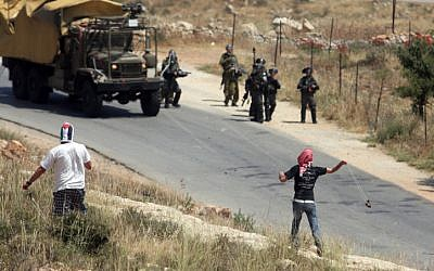 Palestinian protesters throw stones towards Israeli border police during a weekly demonstration in the village of Nabi Saleh near Ramallah. (photo credit: Issam Rimawi/Flash90)