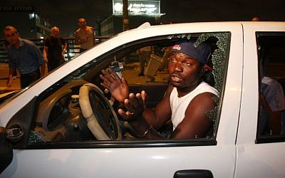 A migrant whose window was smashed during a demonstration in south Tel Aviv Wednesday. (photo credit: Roni Schutzer/Flash 90)