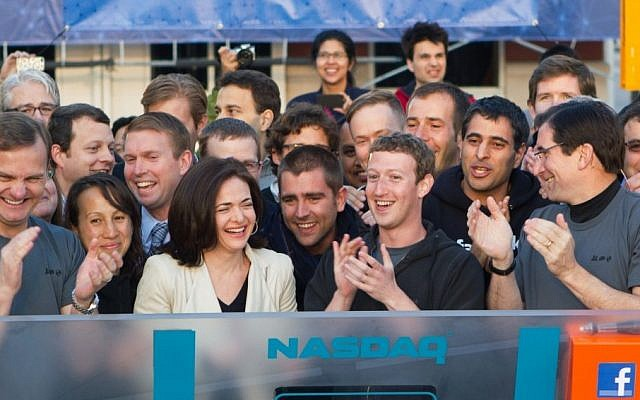 In this image provided by Facebook, Facebook founder, Chairman and CEO Mark Zuckerberg, center, applauds at the opening bell of the Nasdaq stock market, Friday. (photo credit: AP)