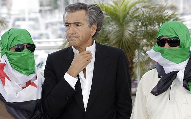 Director Bernard-Henry Levy, centre, flanked by two unidentified persons wearing Syrian flags pose during a photo call for The Oath of Tobruk at the 65th international film festival, in Cannes, southern France, Friday. (photo credit: AP)