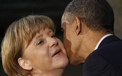 President Barack Obama kisses German Chancellor Angela Merkel on the cheek upon her arrival at the G8 Summit Friday at Camp David, Md. (photo credit: AP/Charles Dharapak)