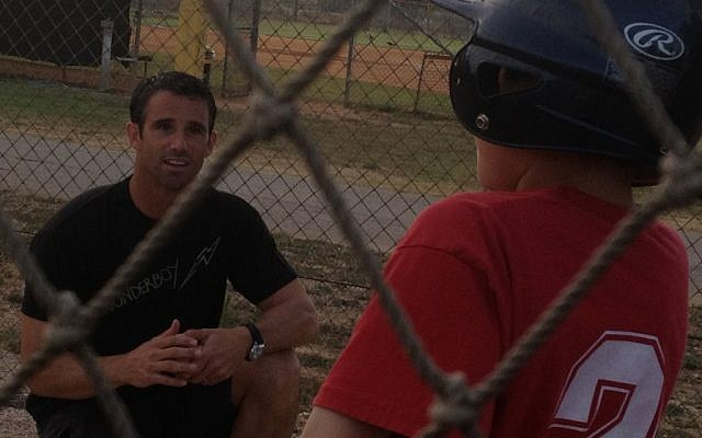 Former All-Star catcher Brad Ausmus gives some pointers to a young Israeli baseball enthusiast (photo credit: Michal Shmulovich)