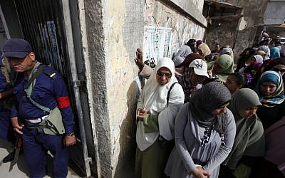 A Navy officer stands guard as Egyptian women line up outside a polling station to cast their votes during the first day of the presidential elections in Alexandria, Egypt, on Wednesday, May 23, 2012 (photo credit: AP/Khalil Hamra)