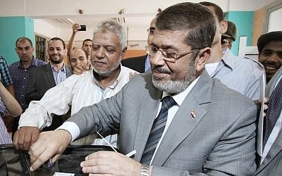 Muslim Brotherhood presidential candidate Mohammed Morsi casts his vote at a polling station in Zakazik, 80 Kilometers (50 miles) north of Cairo on Wednesday. (photo credit: Ahmed Gomaa/AP)