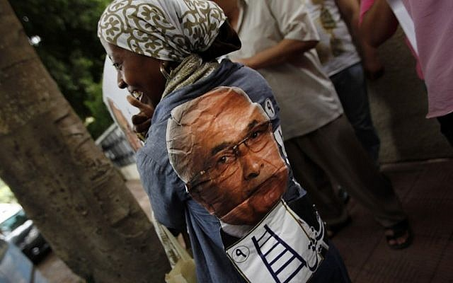 An Egyptian woman wears a shirt with presidential candidate Ahmed Shafiq's face on the back Saturday. (photo credit: AP Photo/Khalil Hamra)