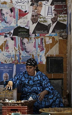 An Egyptian street vendor sells fruits in front of a wall filled with defaced posters of presidential candidates in Cairo, Egypt, Monday, May, 21, 2012 (photo credit: AP/Hasan Jamali)