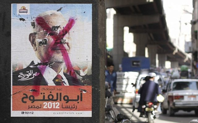 Egyptians pass by a defaced poster of a presidential candidate, Abdel-Moneim Abolfotoh in Cairo, Egypt, Monday, May, 21, 2012 (photo credit: AP/Hasan Jamali)