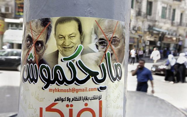 """Egyptians walk near a poster showing ousted president Hosni Mubarak, center, and presidential candidates Amr Moussa, left, Mubarak's foreign minister for 10 years, and Ahmed Shafiq, a former Air Force commander and civil aviation minister whom Mubarak made prime minister during his last days in power, with Arabic that reads, """"they will not rule,"""" in Cairo, Egypt, Monday, May 21, 2012 (photo credit: AP/Amr Nabil)"""