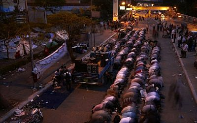 Followers of Egyptian Muslim cleric and former candidate for Egyptian presidency, Hazem Salah Abu Ismail, pray at the location of their sit in on the road leading to the Defense Ministry, in Cairo, Egypt. (photo credit: AP/Fredrik Persson)